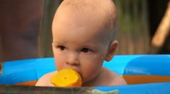 Footage infant boy swimming in pool and play with fish toy Stock Footage