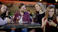 Young woman is watching something in the cellphone sitting with her friends in Stock Footage