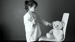 Child role playing doctor with teddybear Stock Footage