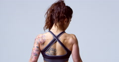 Back view of muscular dark haired woman with tattoos, shot on R3D Stock Footage