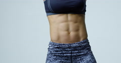 Close-up shot of muscular young woman's mid-section and abs, shot on R3D Stock Footage