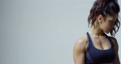 Muscular woman in sports clothing flexing bicep to camera, shot on R3D Stock Footage