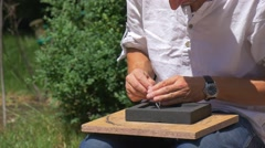 Man is Grinding a Mold Blank Outdoors Sunny Day Casting Molds Craftsmen Making Stock Footage