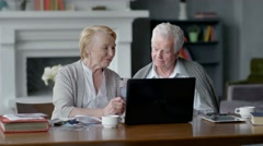 Senior couple websurfing on internet with laptop. Happy elderly man and woman Arkistovideo