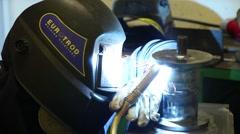 Man with welding helmet welding steel Stock Footage