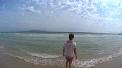Girl enjoying her beach lifestyle walking by aqua colored ocean, Majorca, Spain Stock Footage