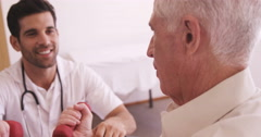 Male doctor assisting senior man to exercise Stock Footage