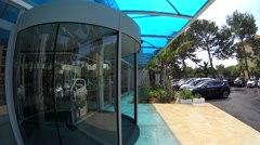 Revolving glass door at the entrance of luxury hotel lobby, sun after rain Stock Footage