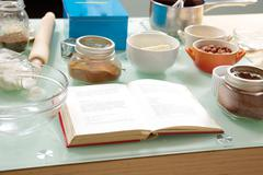 Cookbook on table ingredients cups bowls Stock Photos