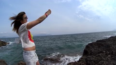 Woman in sunglasses and mini skirt stand on rock and take selfie Stock Footage