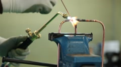 Plumber sweating a copper pipe with a propane torch to weld solder joint Stock Footage