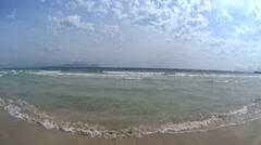 Girl at beach walking in white t-shirt and pink bikini splashing in sea shallows - stock footage