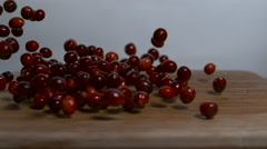 Static shot of cranberries being dropped onto a cutting board in slow motion. - stock footage