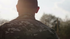 Army soldier walking confident in sunset scene Stock Footage