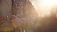 Commando solider charges rifle ammunition clip at sunset Stock Footage