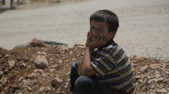 Syrian war refugee boy sits and looks at the camera Stock Footage