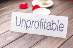 Unprofitable to profitable on white paper Stock Photos