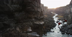 Tracking shot past winding river in a dark canyon along a clif in slow motion Stock Footage