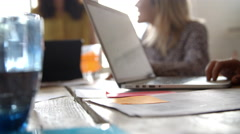Designers Meeting Around Table With Laptop In Foreground Stock Footage