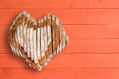 Yummy loaf shaped as heart over orange paneling Stock Photos