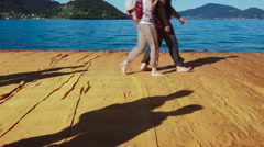 People walking along The Floating Piers, walkway on Iseo Lake made by Christo Stock Footage