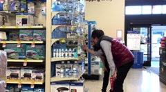 Couple buying siamese fighting fish inside Petsmart store Stock Footage