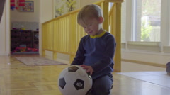 Cut boy doesn't know what to do with his soccer ball Stock Footage