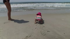 Baby and her mother playing in the sand at the ocean beach on a summer day, 4K - stock footage