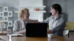 Grandson Teaching Grandmother How to Use a laptop PC. they smile and laugh Stock Footage