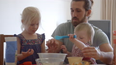 Father With Daughters At Home Baking Cakes Together Stock Footage