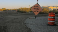 Roadwork Ahead Sign sits on Fresh Asphalt by a Traffic Barrel Stock Footage