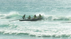 Backlit shot of surf boats battling waves in a race Stock Footage