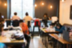 Blurry defocused image of people working in cafe Stock Photos