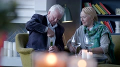 Elderly man sitting with his wife and open bottle of wine Stock Footage
