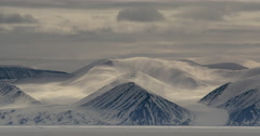 Time lapse - clouds cast shadows over snowy mountains sea ice Stock Footage