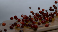 Cranberries being dropped onto a cutting board in slow motion. Stock Footage