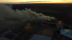 Large building fire viewed from the sky at sunset Stock Footage