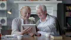 Happy lovely retired couple use tablet computer and laugh Stock Footage