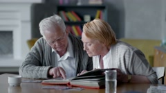 Elderly happy couple spend time together and nostalgic. they looking old photo Stock Footage