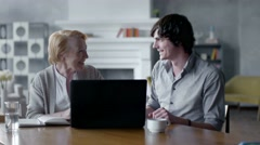 Grandson Teaching Grandmother How to Use a laptop PC. they smile and laugh - stock footage