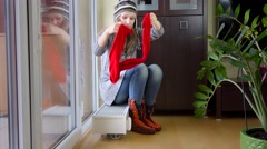 Hot woman undress cap and scarf sitting on radiator. Temperature rising - stock footage