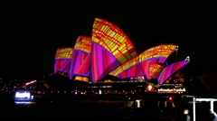 Sydney Opera House and Vivid Light Show and ferries passing in foreground. Stock Footage