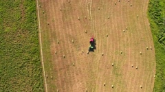 Aerial beautiful shot high clip as farmer cuts and bails hay Stock Footage