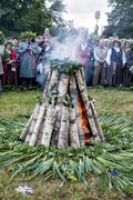 Crowd of people around bonfire celebrating Midsummer summer solstice Kuvituskuvat