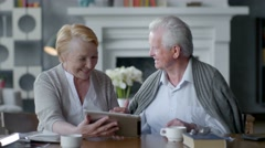 Happy lovely retired couple use tablet computer. They having fun in Stock Footage