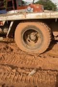 Mud Covered Truck Tire and flatbed on muddy site with Plastic bottle - stock photo