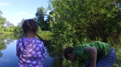 Teen boy and girl child tear the grass on the bank of the pond. - stock footage