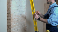 Worker checking the yellow level on the concrete wall and doing measures Stock Footage