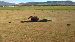 Aerial dolly shot as farmer cuts and bails his hay Stock Footage