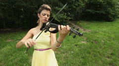 Female classical musician plays electric violin outdoors Stock Footage